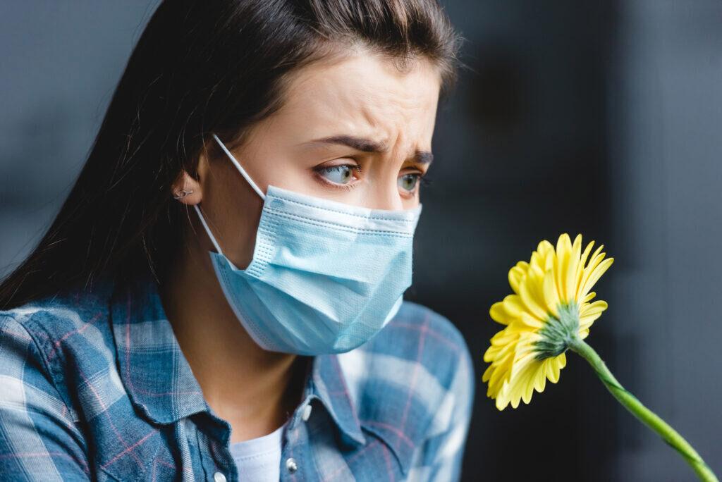 Αλλεργική ρινίτιδα , γυναίκα φορώντας μάσκα αδυνατεί να μυρίσει ένα λουλούδι